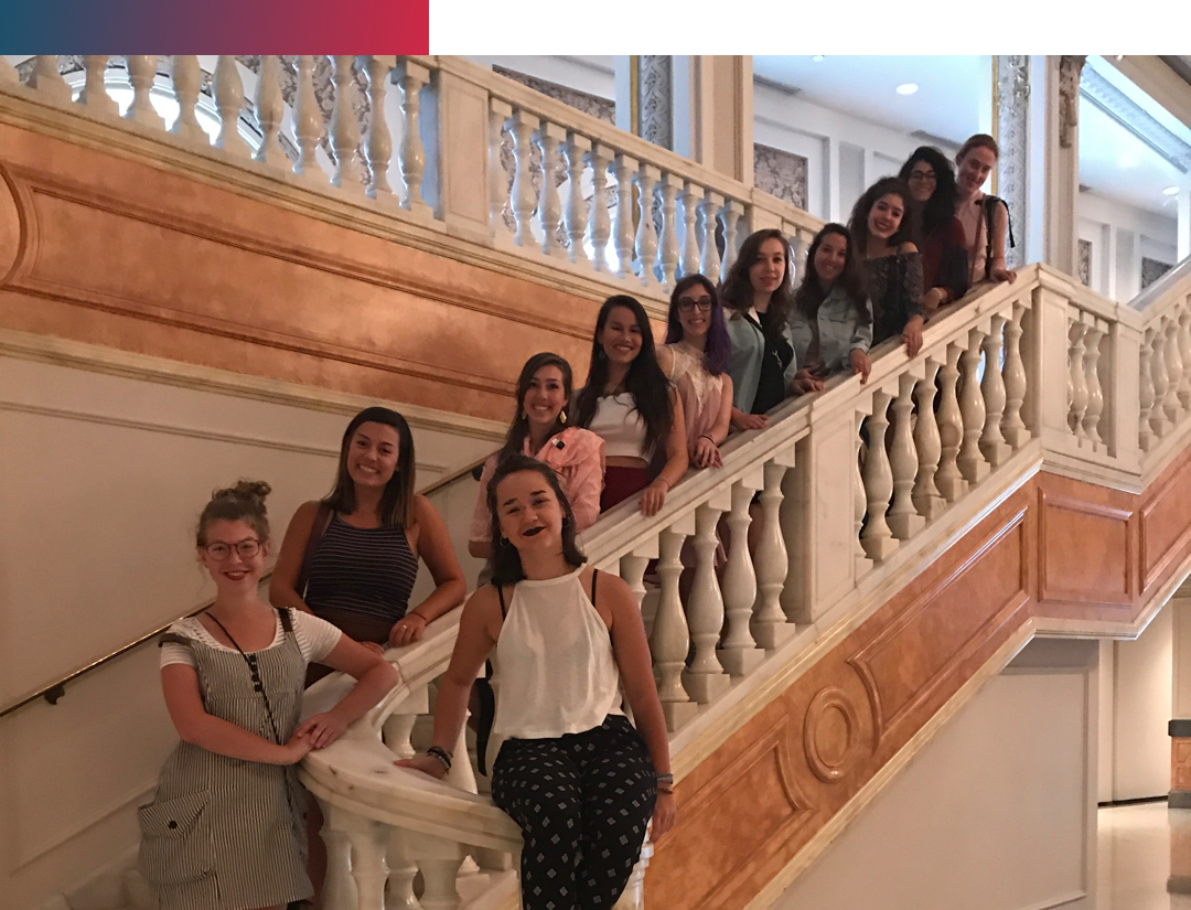 a group of female students standing on a marble staircase